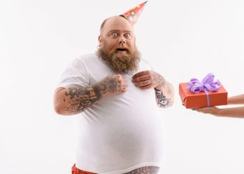 Fat man is receiving gift box. He is standing and looking at camera with surprise. Man is wearing birthday cone. Isolated