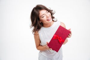 Portrait of a laughing woman holding gift box isolated on a white background